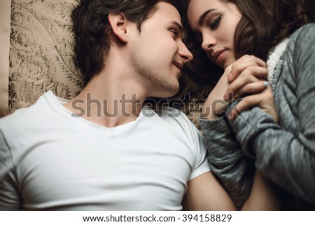 beautiful brunette young woman and guy lying in bed and holding tightly hands. The concept of tenderness and affection #394158829