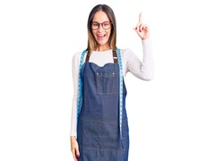 Beautiful brunette young woman dressmaker designer wearing atelier apron pointing finger up with successful idea. exited and happy. number one.