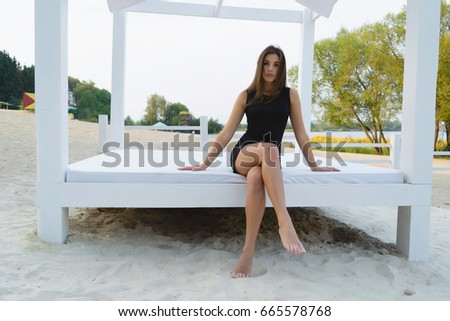 Beautiful brunette young woman in a black dress posing on the beach #665578768