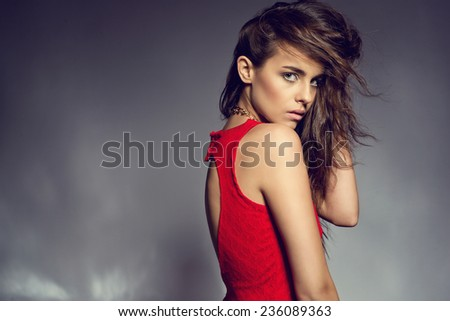 Beautiful brunette young woman in elegant evening red dress. Posing on shining mirror floor