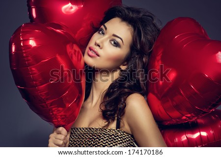 Stock Photo Beautiful brunette young woman in golden dress with a heart-shaped balloons. Valentine's day