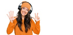 Beautiful brunette young woman listening to music using headphones showing and pointing up with fingers number eight while smiling confident and happy.
