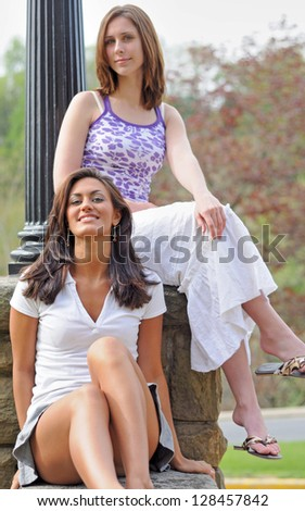Beautiful brunette young woman sitting in front of a female friend on a rock ledge beneath a light pole - on campus - coeds