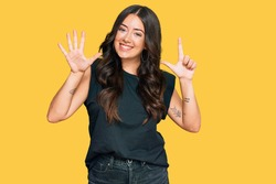 Beautiful brunette young woman wearing black shirt showing and pointing up with fingers number seven while smiling confident and happy.