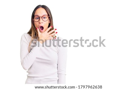 Beautiful brunette young woman wearing casual white sweater and glasses looking fascinated with disbelief, surprise and amazed expression with hands on chin  Photo stock ©