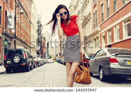 Beautiful brunette young woman wearing dress and walking on the street - stock photo