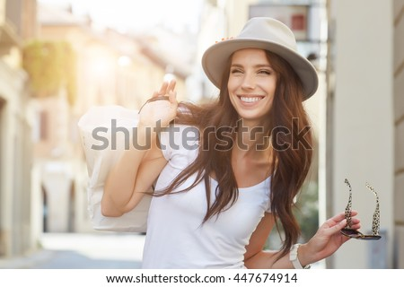Stock Photo Beautiful brunette young woman wearing dress and walking on the street