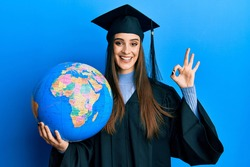 Beautiful brunette young woman wearing graduation robe holding world ball doing ok sign with fingers, smiling friendly gesturing excellent symbol