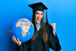 Beautiful brunette young woman wearing graduation robe holding world ball pointing thumb up to the side smiling happy with open mouth