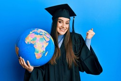 Beautiful brunette young woman wearing graduation robe holding world ball screaming proud, celebrating victory and success very excited with raised arm