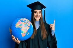 Beautiful brunette young woman wearing graduation robe holding world ball smiling happy pointing with hand and finger to the side