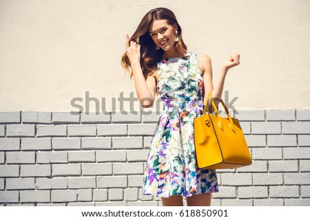 Beautiful brunette young woman wearing nice dress, yellow handbag, walking on the street. Fashion city photo. Flower pattern