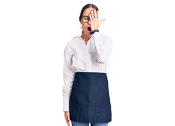 Beautiful brunette young woman wearing professional waitress apron yawning tired covering half face, eye and mouth with hand. face hurts in pain.