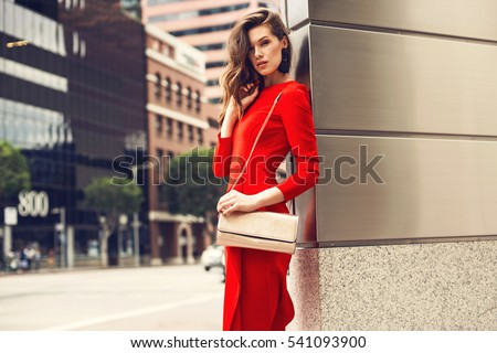 https://image.shutterstock.com/display_pic_with_logo/1125836/541093900/stock-photo-beautiful-brunette-young-woman-wearing-red-dress-golden-purse-walking-on-the-street-fashion-photo-541093900.jpg