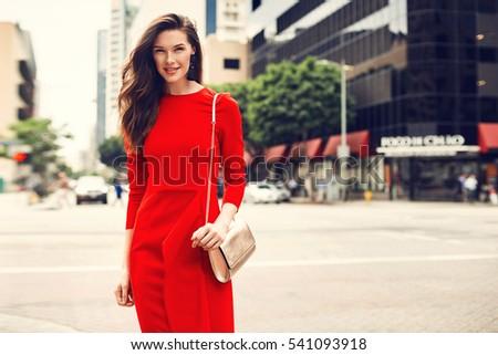 Beautiful brunette young woman wearing red dress, golden purse, walking on the street. Fashion photo