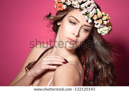 beautiful brunette young woman with wreath of flowers studio shot pink background