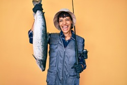Beautiful brunettte fisher woman holding fishing rod and raw salmon smiling and laughing hard out loud because funny crazy joke.