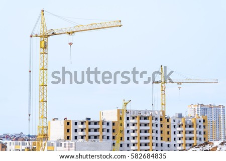 beautiful building and a successful business build tall buildings for residents. standing next to a construction crane. #582684835
