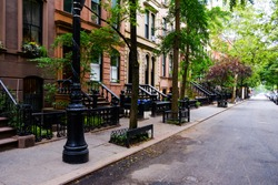 Beautiful buildings in Greenwich Village, Soho district. Entrance doors with stairs and trees, Manhattan New York. Classic luxury apartment building in New York City. Beautiful american street.