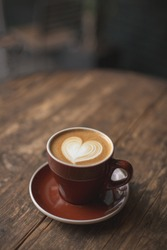 Beautiful burgundy cup of cappuccino with trendy heart shape latte art. Summer loft cafe background. Urban space. Drinking coffee on the terrace.