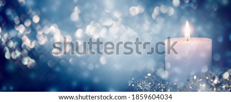 Photo of  beautiful burning candlelight on abstract blurred background, shiny christmas lights at blue night, advertising space on xmas concept