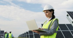 Beautiful business lady standing among field of solar panels in special uniform. Female engineer uses laptop to work outside.