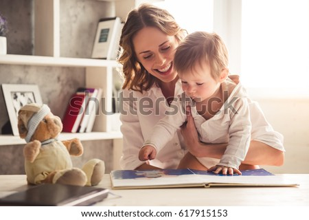 Beautiful business mom in suit is reading a book with her cute baby boy and smiling, at home