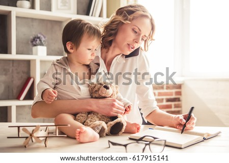Beautiful business mom is talking on the mobile phone and taking notes while spending time with her cute baby boy at home