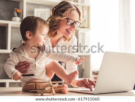 Beautiful business mom is using a laptop and smiling while spending time with her cute baby boy at home #617915060