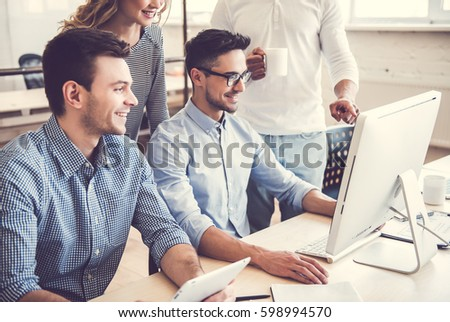 Beautiful business people are using computers and smiling while working in office #598994570