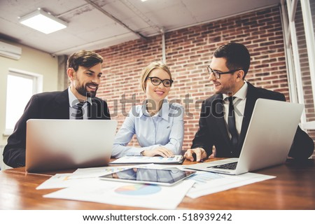 Beautiful business people are using laptops, studying documents, talking and smiling while working in office