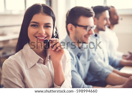 Beautiful business people in headsets are using computers and smiling while working in office. Girl is looking at camera