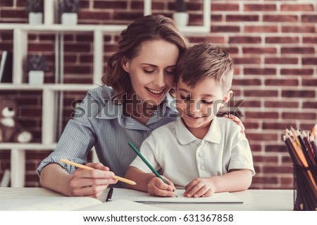 Beautiful business woman and her cute little son are drawing and smiling while sitting in office #631367858