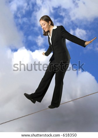 beautiful business woman balancing on rope with the sky at the background