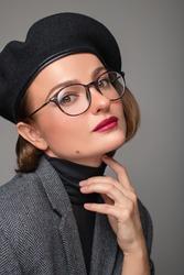 Beautiful business woman brunette in black beret and eyeglasses. Checking new eyeglasses