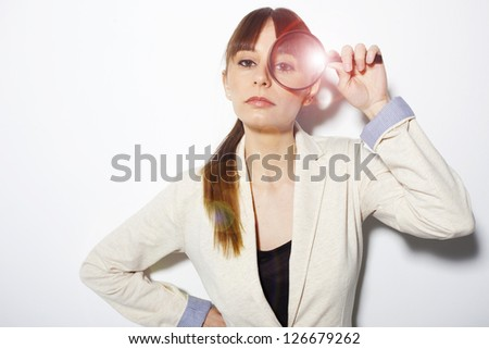 Beautiful business woman holding magnifying glass. Attractive young business woman with a magnifying glass
