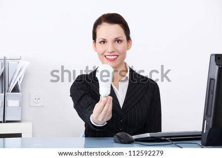 Beautiful business woman in office holding energy saving eco bulb.