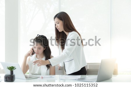Beautiful business woman is pointing a pen to notebook computer for advising her subordinate or colleague to solve a problem. Charming beautiful businesswoman call her boss or customer for the problem