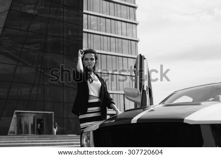 Beautiful business woman on the background of the modern office near the sport car