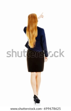 Beautiful business woman pointing up.