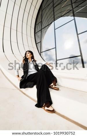 beautiful business woman sits on a window background