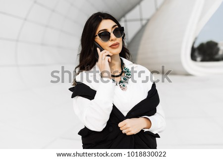 beautiful business woman speaks by phone on building background