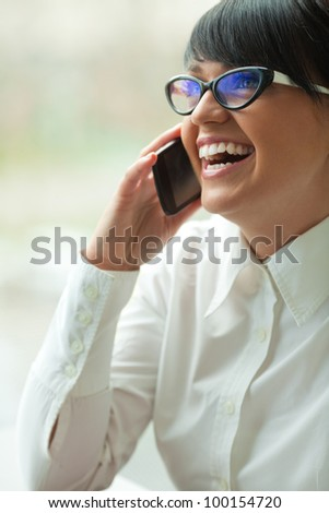 Beautiful business woman talking by phone at office.