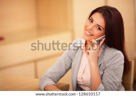 Beautiful business woman talking on cell phone and looking at camera