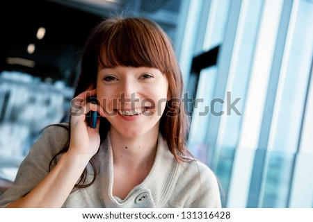 Beautiful business woman talking on mobile phone and smiling, looking at camera