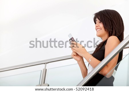 Beautiful business woman texting on her cell phone