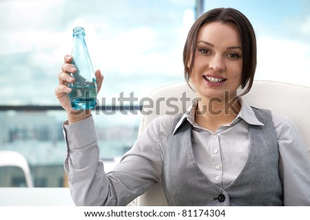 Beautiful business woman thinking about something while drinking cool fresh mineral water at her office