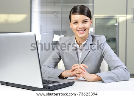 Beautiful business woman thinking about something while working on computer at her office