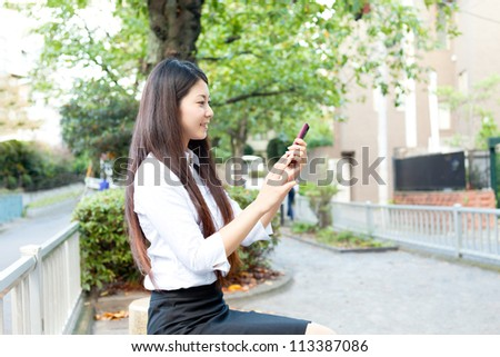 Beautiful business woman using a cellular. Portrait of asian.