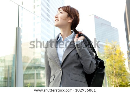 Beautiful business woman walking outside her office. Portrait of